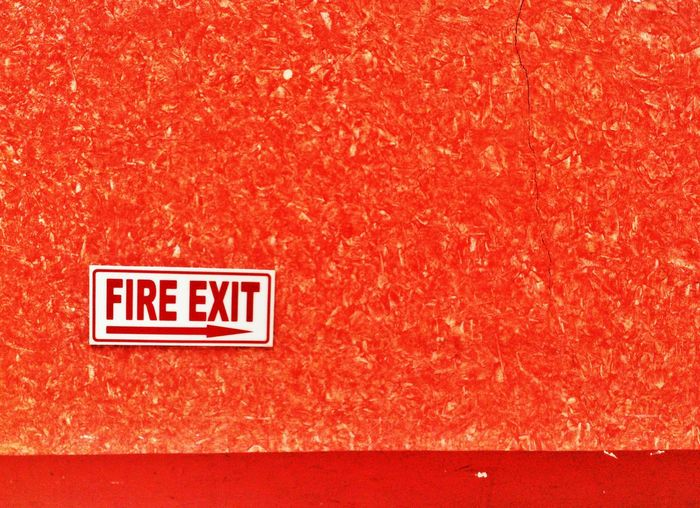 Fire exit sign board on wall