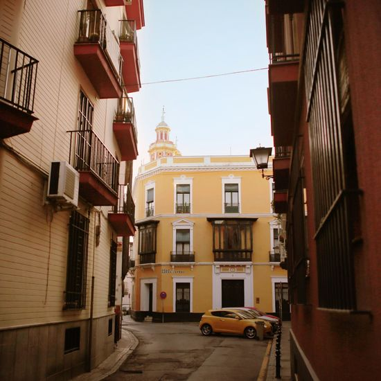 Yellow building and yellow car España Travelling Europe SPAIN Seville Building Exterior Architecture Built Structure Residential Building Outdoors Street Window No People Road City Clear Sky
