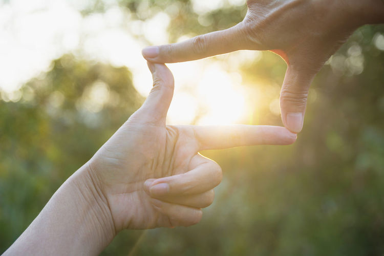 Body Part Brightly Lit Close-up Day Finger Focus On Foreground Hand Holding Human Body Part Human Finger Human Hand Human Limb Leisure Activity Lens Flare Lifestyles Nature One Person Outdoors Personal Perspective Real People Sunlight Unrecognizable Person