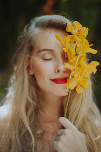 Beautiful Woman Beauty Blond Hair Close-up Day Flower Focus On Foreground Front View Headshot Leisure Activity Lifestyles Long Hair One Person Outdoors Real People Smiling Young Adult Young Women Fresh On Market 2017