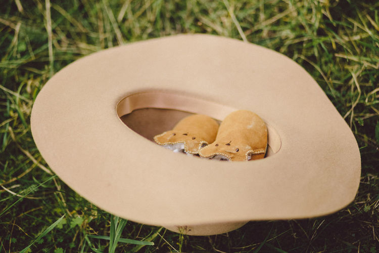 High Angle View Of Baby Booties In Hat On Grass