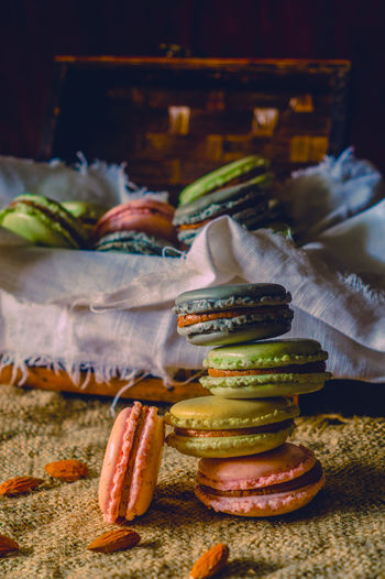 Stack of colorful macaroons with almonds on jute fabric