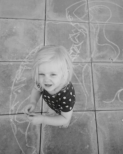 Portrait of girl standing by chalk drawing on floor
