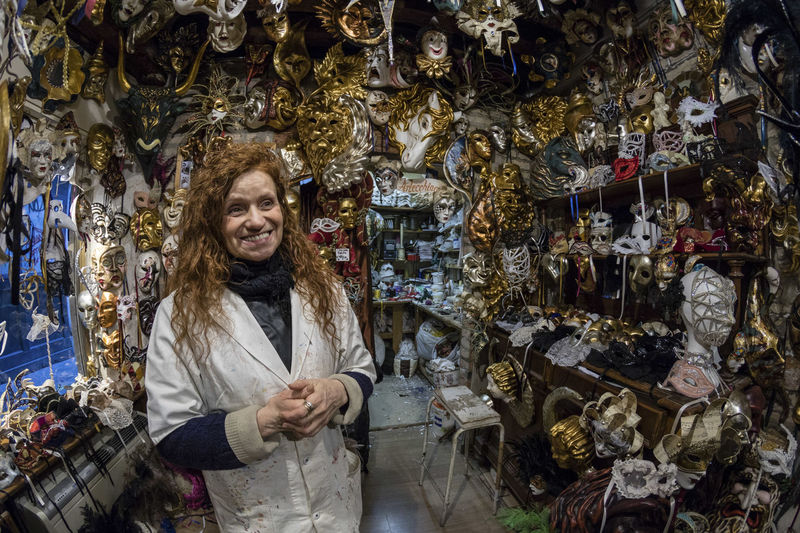 Woman Smiling While Standing Amidst Masks In Store