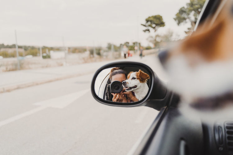 Woman photographing reflecting on side-view mirror