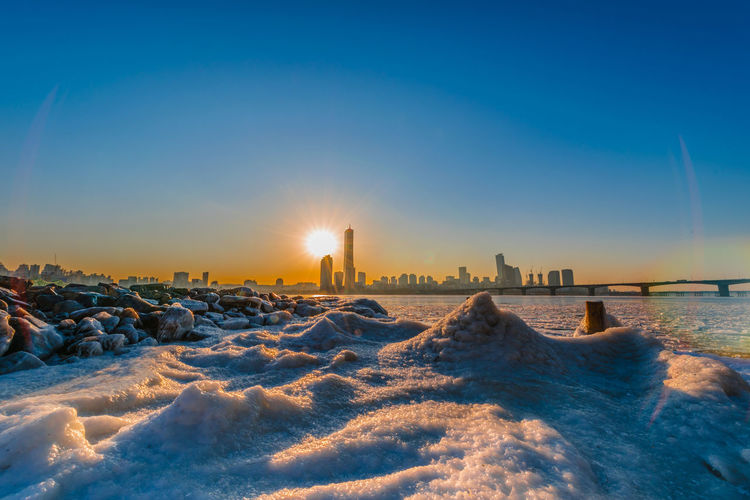 Evening sunset at the Han River in winter South Korea Architecture Beauty In Nature Building Exterior Built Structure Clear Sky Cold Temperature Land Nature No People Scenics - Nature Sea Sky Snow Sun Sunlight Sunset Water Winter