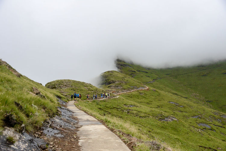 Hikers Walking On Mountain During Foggy Weather