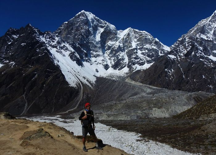 Man standing with snowcapped mountains during winter