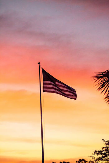 Red, white and blue American flag blows in the wind at sunrise American American Flag Forth Of July Patriotic USA Day Flag Flag Pole Independence Day Low Angle View Nature No People Outdoors Patriotism Red White And Blue Sky Stars And Stripes Sunset
