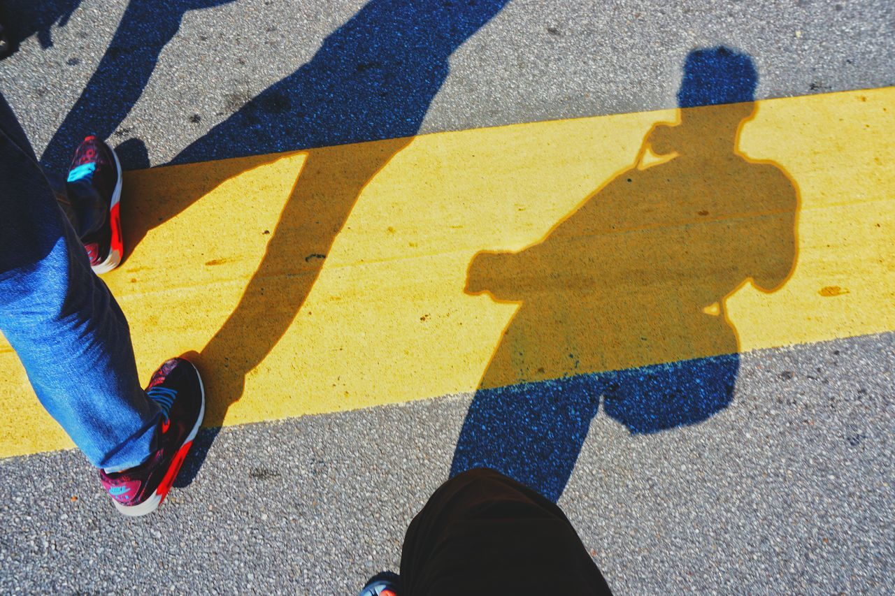 Low section of man with shadow walking on street