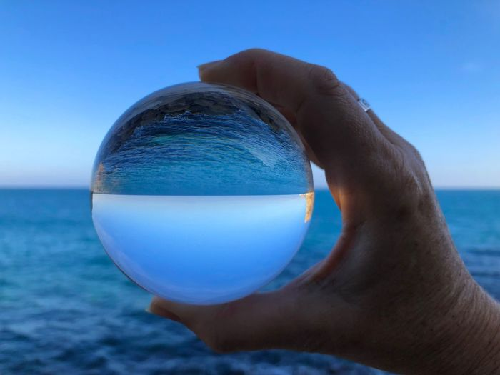 Midsection of person holding crystal ball against sea