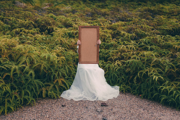 Bride holding empty picture frame while sitting by plants on field