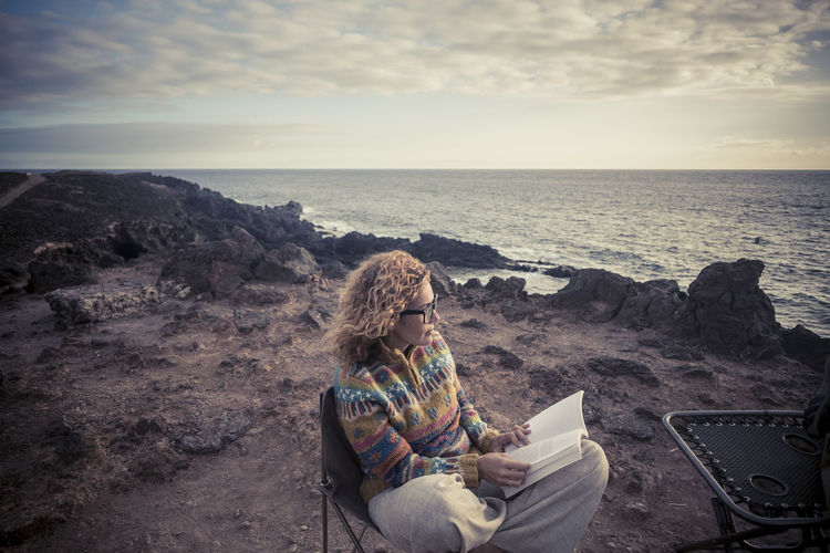 Woman Reading Book While Sitting At Beach Against Sky