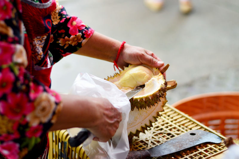 Close-up of woman cutting durian at shop