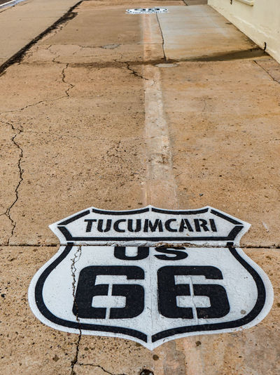 Iconic painted Tucumcari US Route 66 sign on sidewalk in Tucumcari, New Mexico. United States 1960's Communication Cracked Sidewalks Day Iconic Side No People Nostagia Outdoors Route 66 Sidewalk Painted Sig Route 66 Sign Text Tucumcari New Mexico Tucumcari US 66 Sign Painted On Sidewalk Uneven Concrete Sidewalk