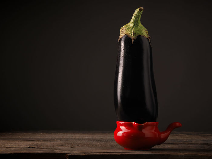 Close-up of red chili pepper on table against black background