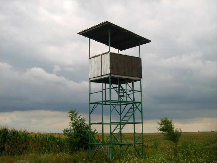 Lookout tower on field against sky