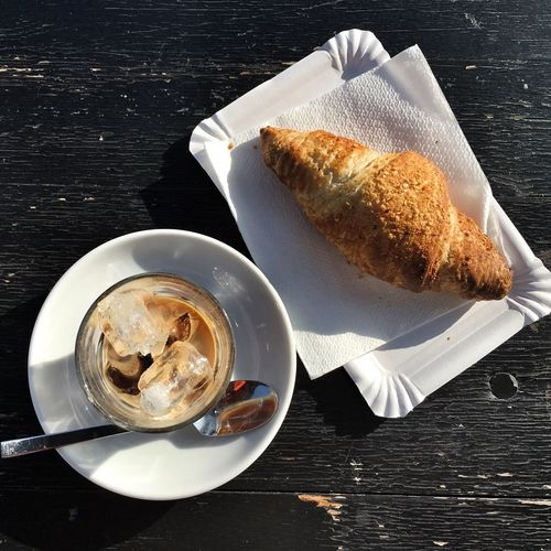 Directly above shot of iced coffee by croissant on table