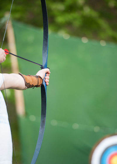 Cropped Image Of Archer Hand Aiming Archery Bow