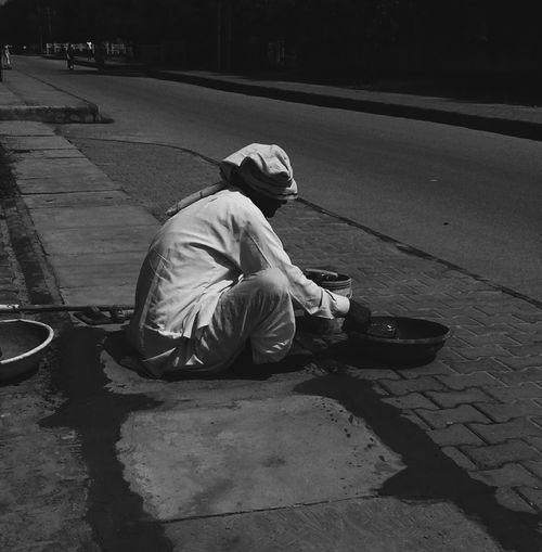 Side View Of Manual Worker Repairing Footpath In City