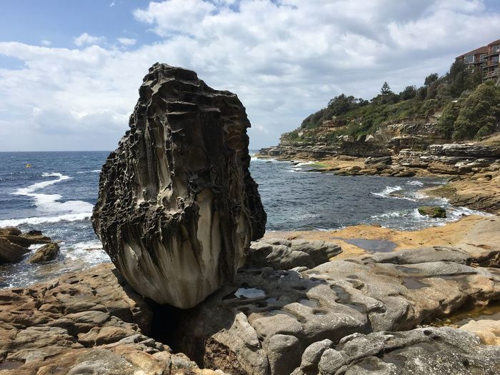 Rock formation on sea shore against sky