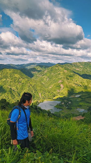 Woman looking at landscape against sky