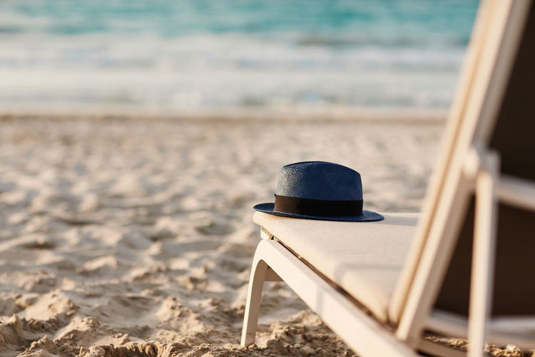 Blue hat is lying on a chaise longue on a beautiful sandy beach by the sea. space for text