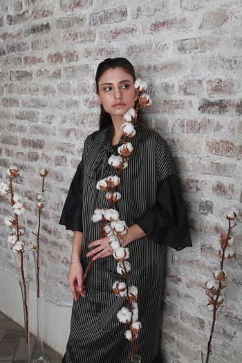 Thoughtful young woman with cotton plant standing against wall