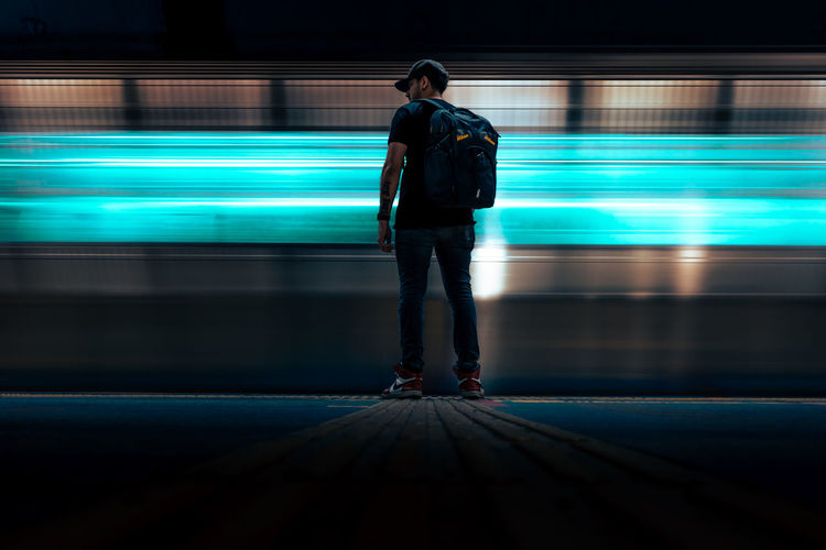Rear view of man walking on illuminated city