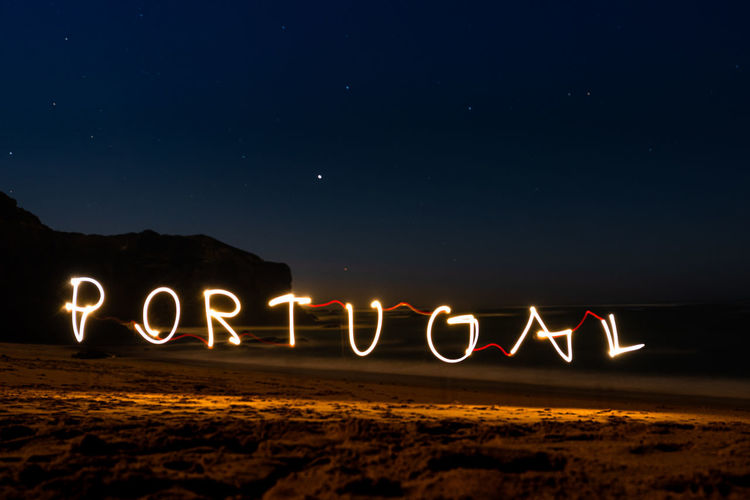 Illuminated light painting forming portugal text at beach
