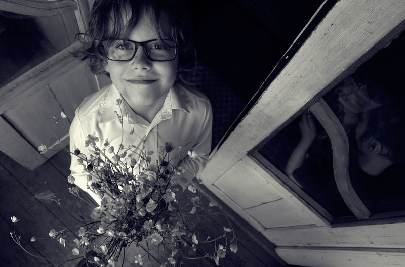 High Angle Portrait Of Smiling Boy Holding Flowers While Standing At Home