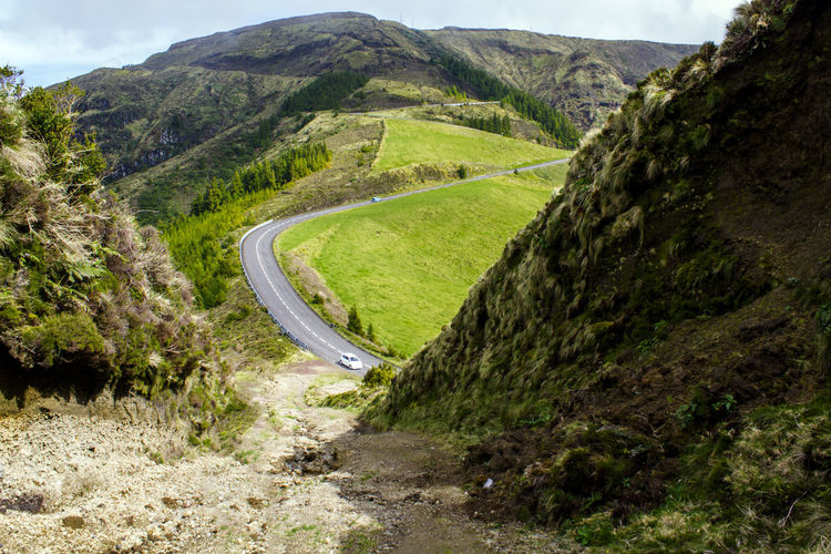 Road going through mountains and green hills Azores Green Color Hiking Rolling Landscape Rural Top Travel Adventure Beauty In Nature Countryside Environment Hill Landscape Mountain Mountain Range No People Non-urban Scene Remote Road Scenics - Nature Top Perspective Top View Tranquil Scene Tranquility Winding Road