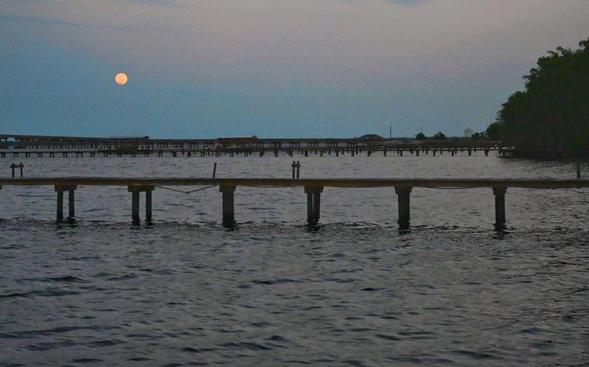 Pier on beach against clear sky at dusk