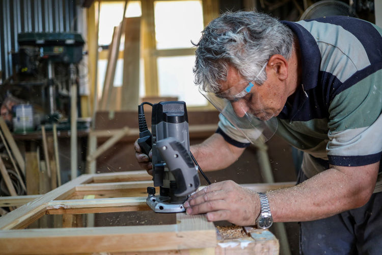 An adult man wearing face mask while working on wood in the shed.