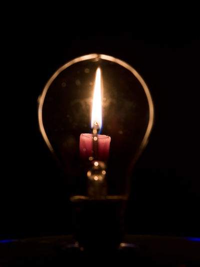 Lightbulb and candle flame Brainstorming Bulb Burn Candle Concept Conceptual Dark Electric Electricity  Energy Filament Fire Flame Flame Glass Idea Illuminated Illumination Incandescence Lamp Light Light-bulb Lightbulb Lighting Equipment Tungsten