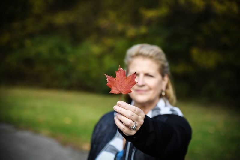 Smiling woman holding maple leaf during autumn