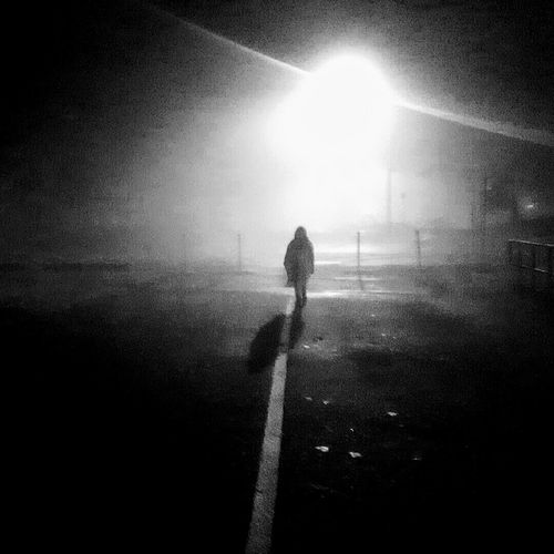 Man standing on road in winter at night