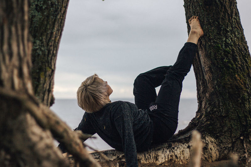 Rear view of woman sitting on tree trunk against sky