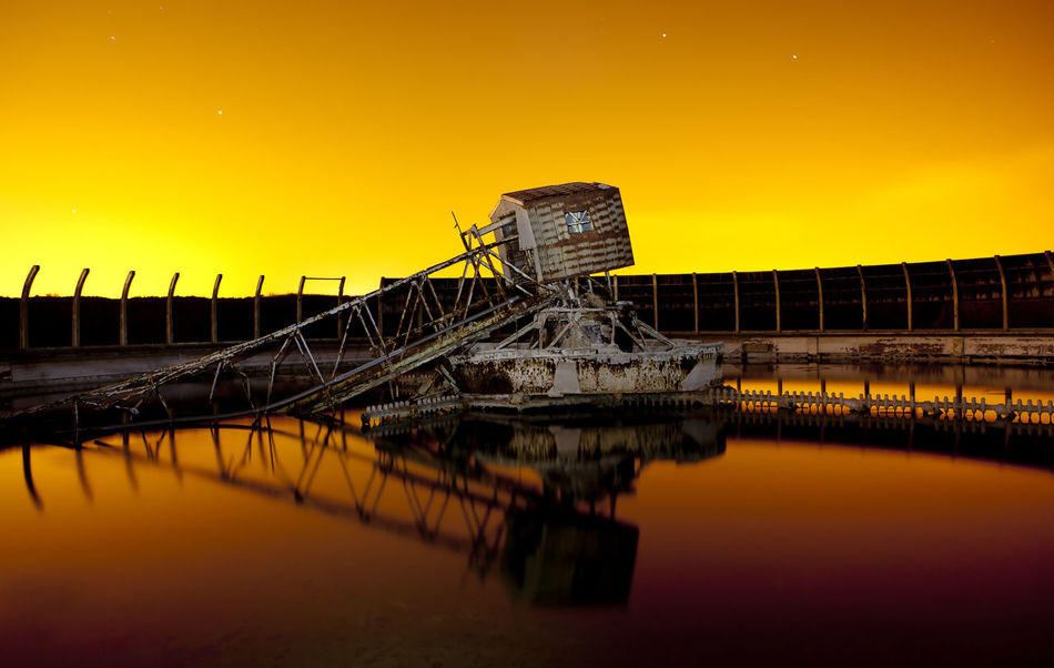 A burning yellow sky provides the backdrop to this industrial decay photograph Burning Sky EyeEmNewHere Industry Night Photography Rust Beauty In Nature Built Structure Clear Sky Fire Gold Colored Horizon Industrial Landscapes Industryporn No People Orange Color Outdoors Pond Reflections Reflection Sea Stars Sunset Water Yellow