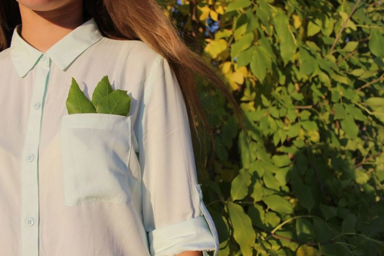 Midsection of woman standing with leaves in pocket