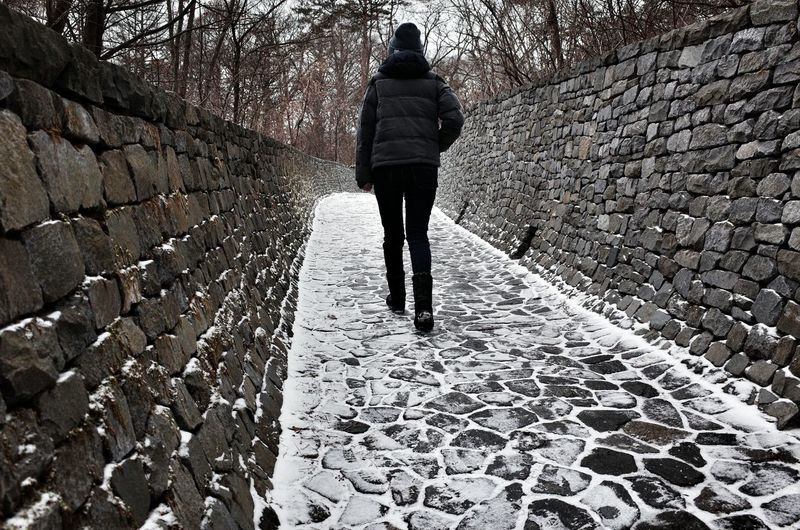 Rear view of woman walking on footpath during winter