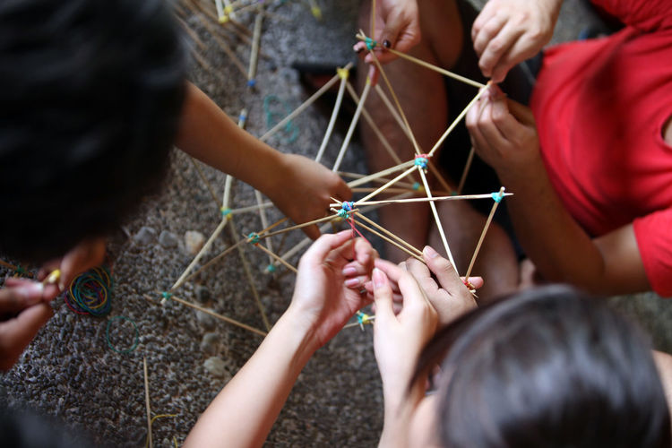 High angle view of friends making model with rubber bands and sticks