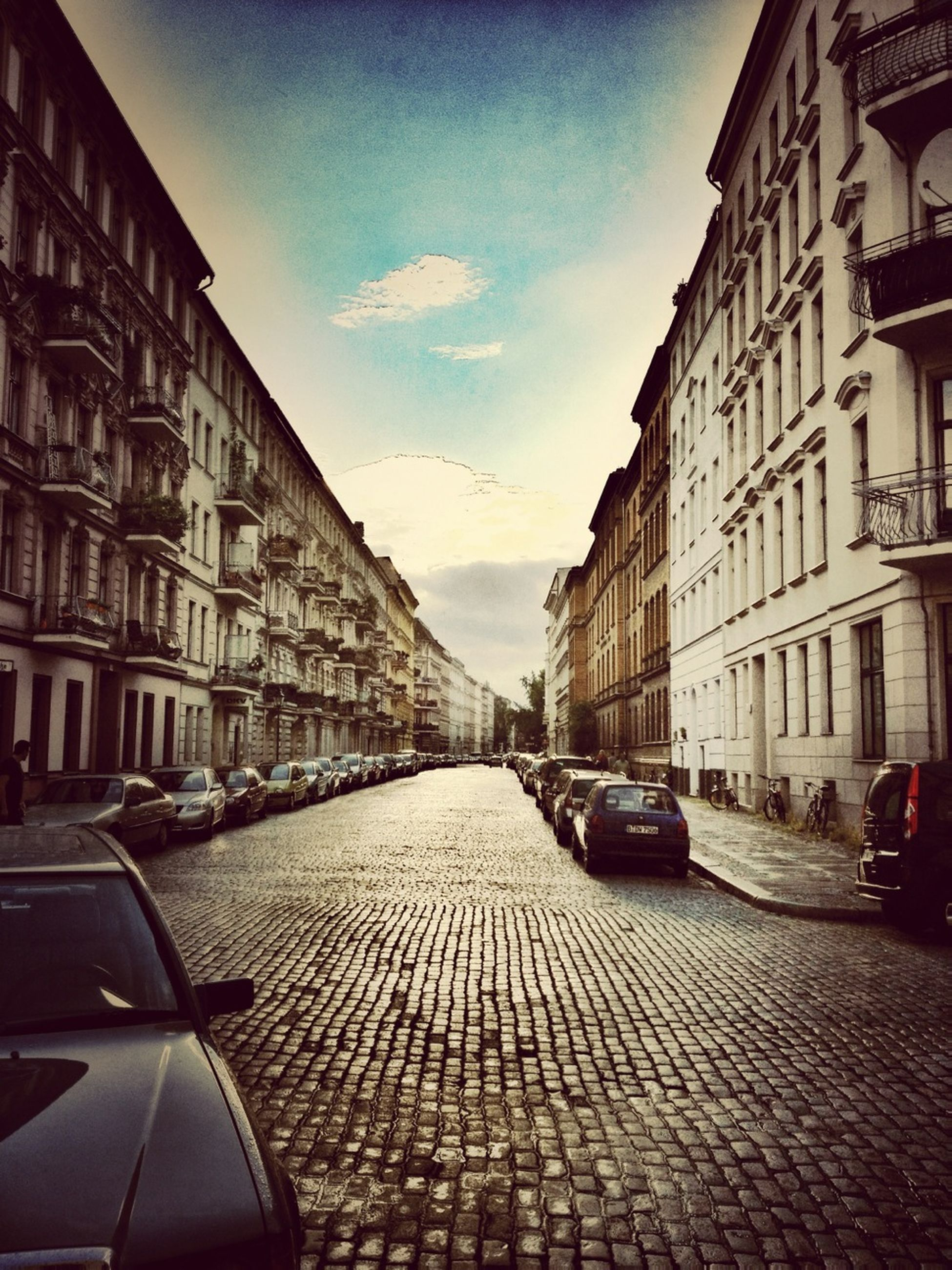 transportation, building exterior, car, architecture, built structure, mode of transport, land vehicle, street, the way forward, city, sky, diminishing perspective, road, vanishing point, road marking, travel, city street, building, cobblestone, day