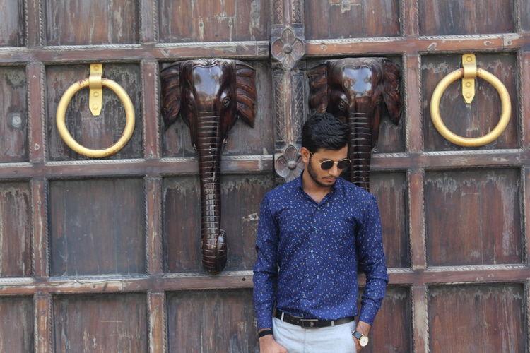 Man wearing sunglasses standing by wooden door