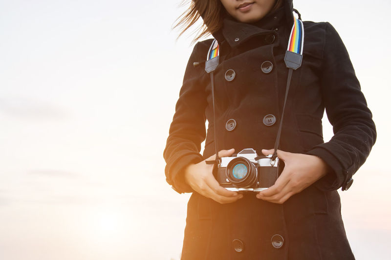 Camera Camera - Photographic Equipment Casual Clothing Day Digital Camera Front View Hairstyle Holding Leisure Activity Lifestyles Midsection Occupation One Person Photographic Equipment Photographing Photography Themes Real People Sky Standing Technology Women
