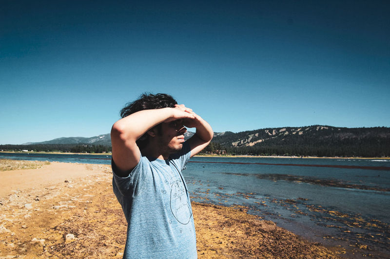 Man shielding eyes while standing at lakeshore against clear sky