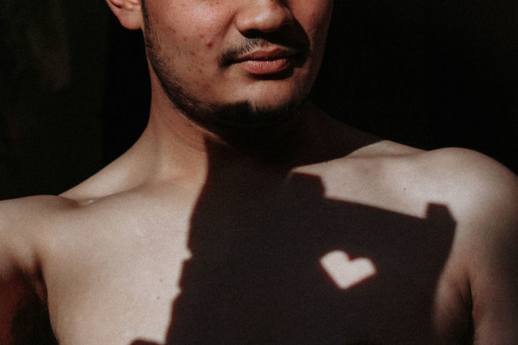 Midsection of shirtless man with heart shaped shadow