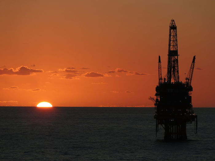 Silhouette oil industry in sea against sky during sunset