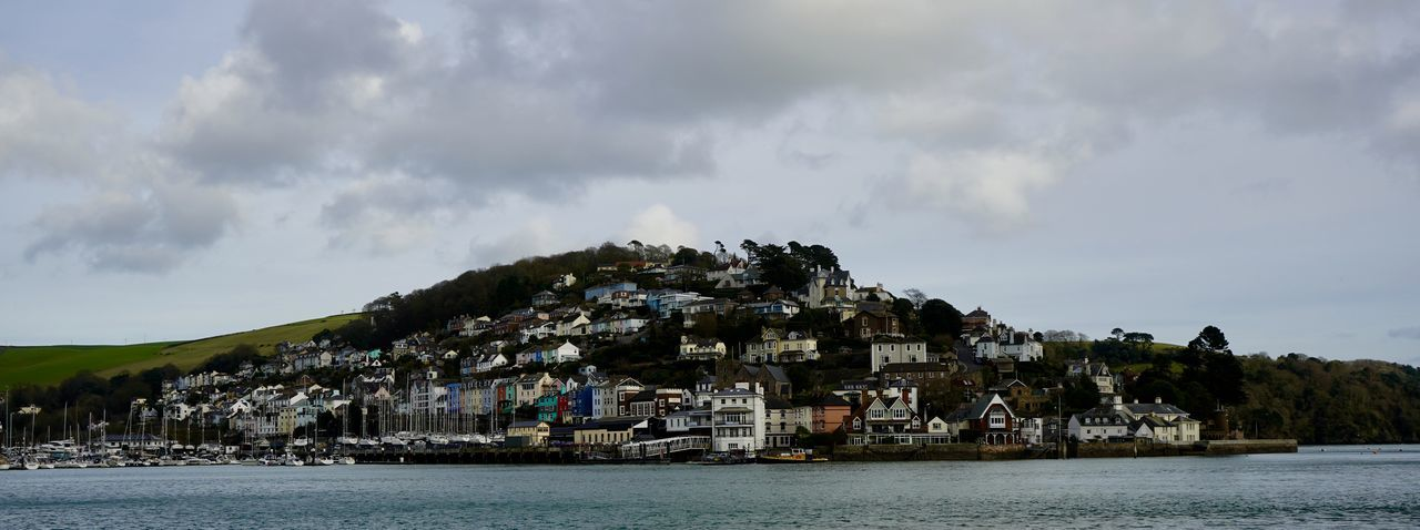 Panoramic shot of townscape by sea against sky