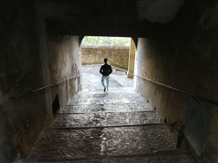 Rear view of man walking on staircase in tunnel